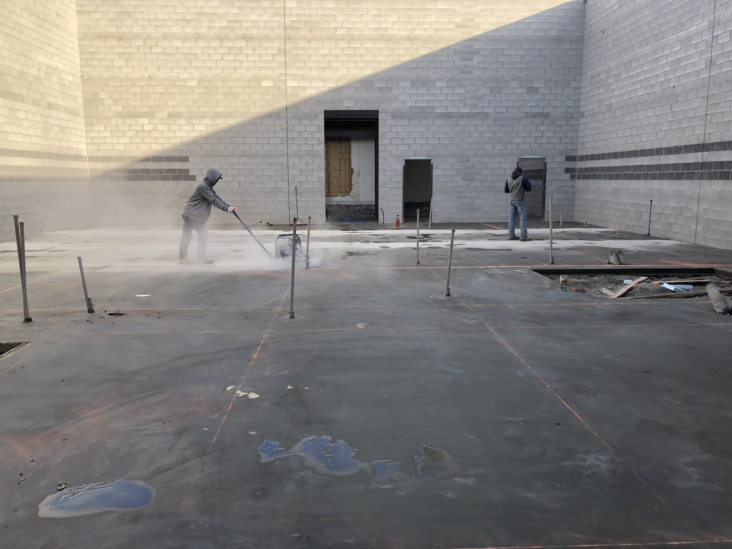 Due to the temperature the slab had blankets over it every night for a week, removed during the day to allow for work. Here they are cutting the expansion joints and control joints between the studio spaces.
