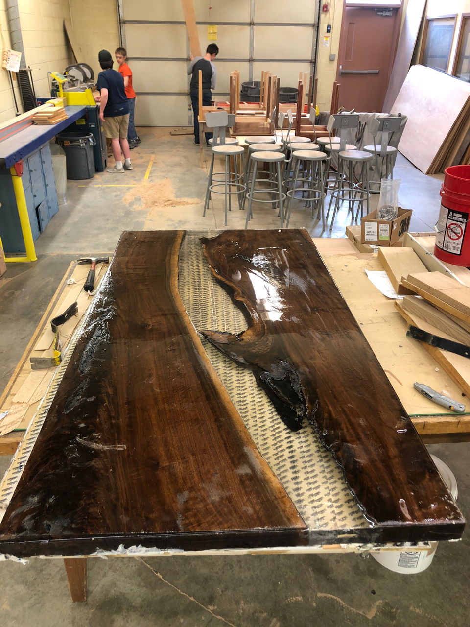 My son has been working on a project in his woods class for the studio. We ordered a huge slap of walnut and a bunch of epoxy and he has been constructing this table for our instrument gallery room. There is still a lot of planing and sanding to be done but it's going to look great.