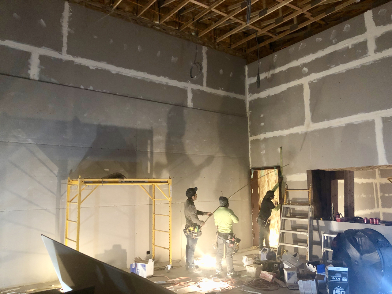 The second level of sheetrock is going up in studio 1. The seems are staggered and the corners are lapped. The opening on the right is the window into control room 1.