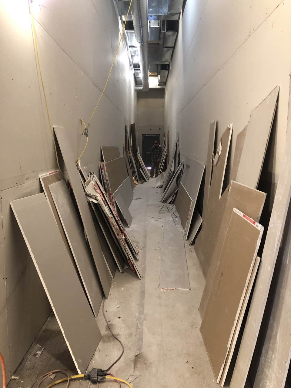 One of the drywall crew workers spends his entire day cleaning up behind the guys hanging the sheets. Still, every day the hallway goes from empty to this.