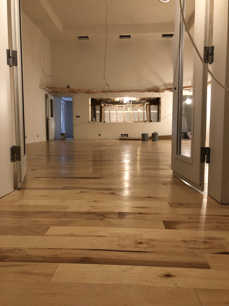 The most exciting thing this week was definitely the arrival and installation of the hickory flooring in studio 1. This photo is looking out of one of the iso booths in studio 1 toward the control room.