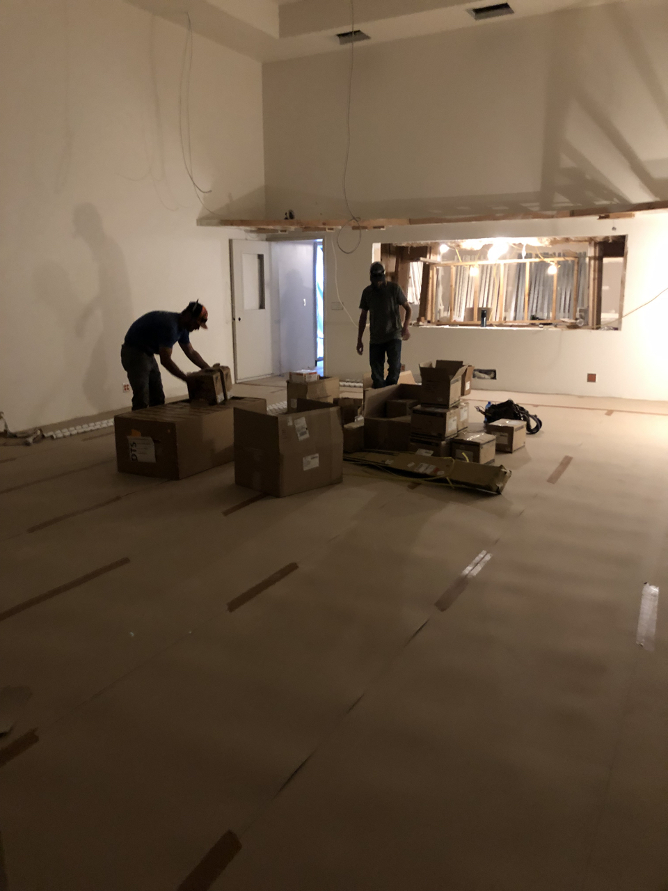 The electricians sorting through a delivery of lighting fixtures in tracking room 1.  The floors have been covered to protect them through the completion of the build.