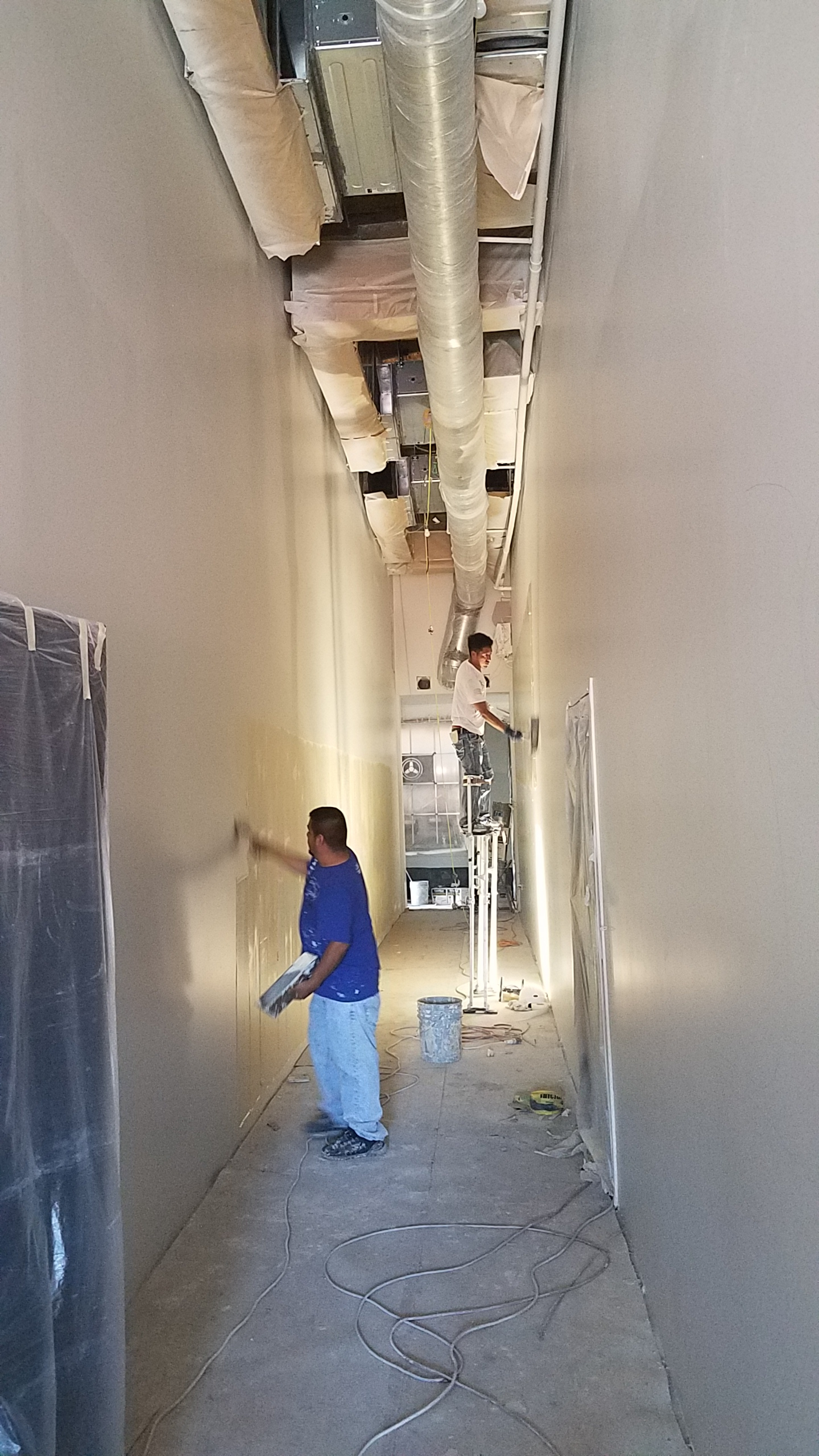 Work on the hallway continues. A crew came and skimmed the entire wall with mud.