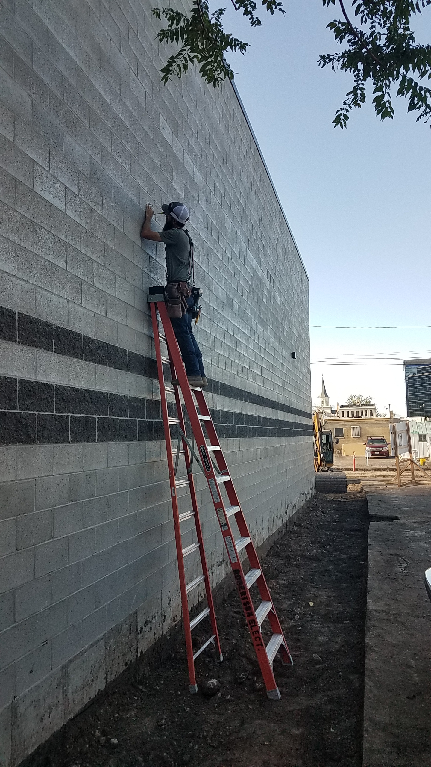 Installing exterior lights along the west wall of the building.