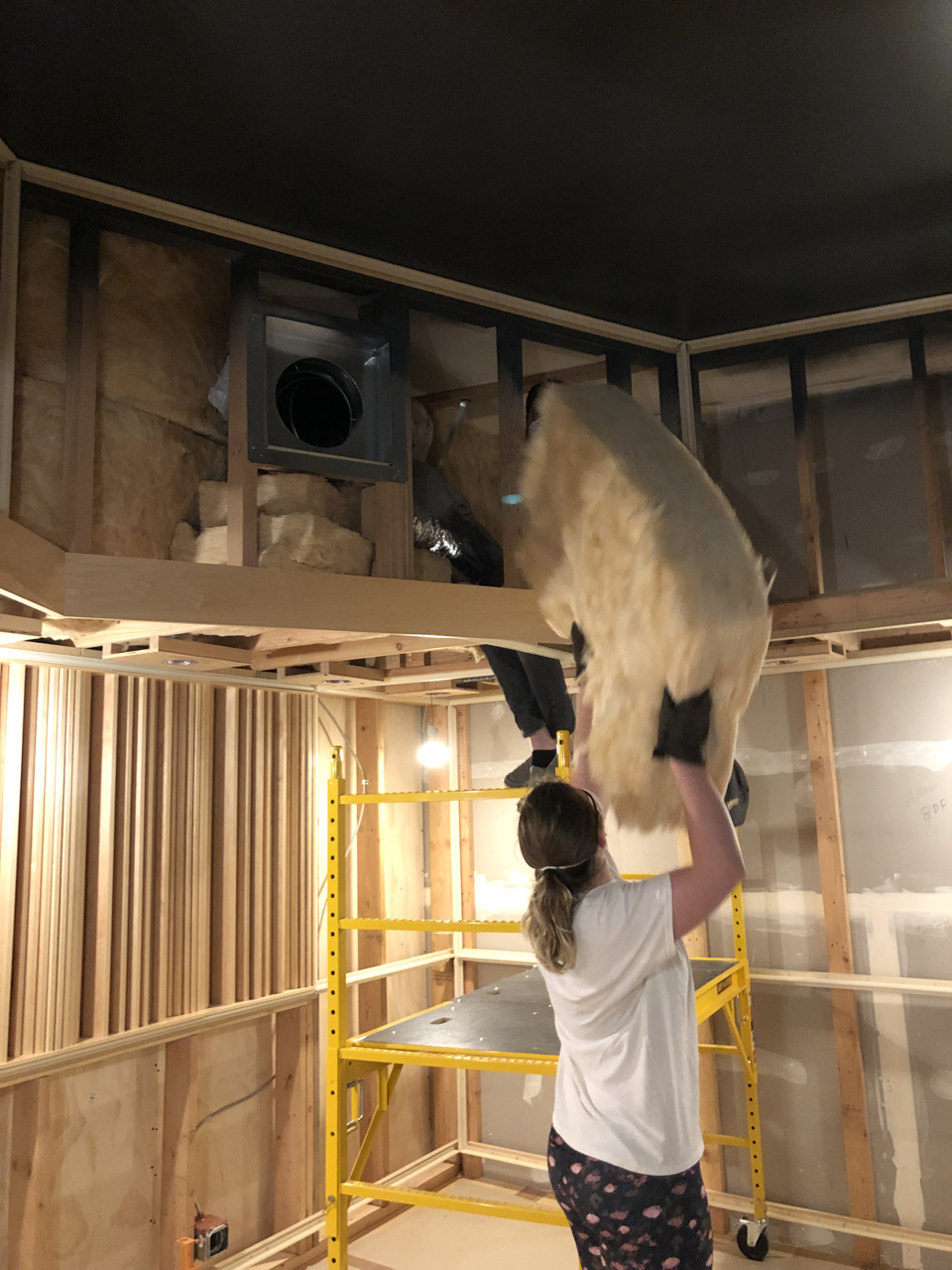 Maren and Nathan, both audio engineers, are placing batting insulation in the upper soffit of control room 2. They have to be careful to fill as much of the cavity as possible without compressing the fiberglass.