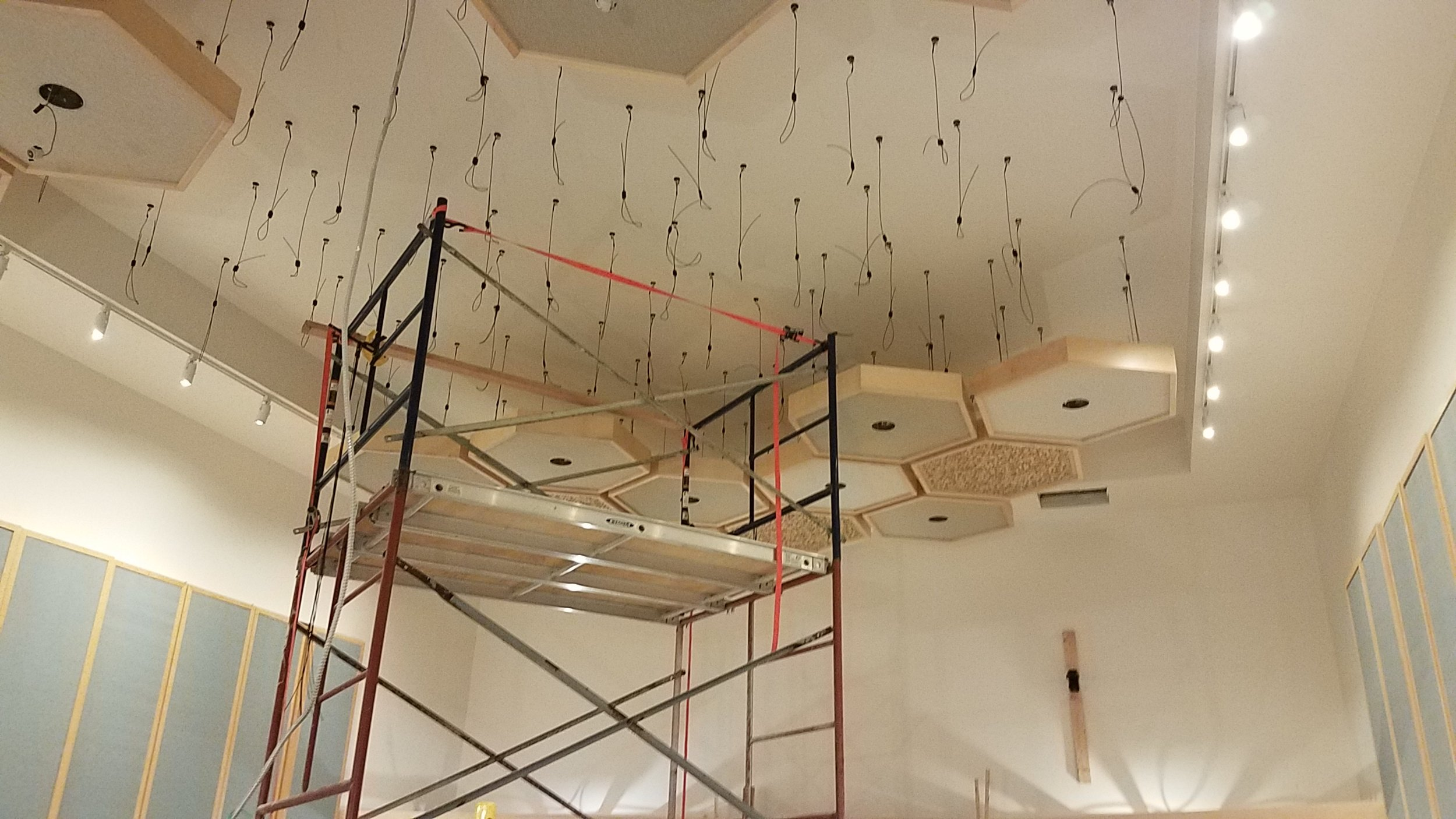 The marks were then transferred to the ceiling with a laser and screws with eyelets were installed in those locations. Then one by one the hexagon shaped clouds were hoisted and hung.
