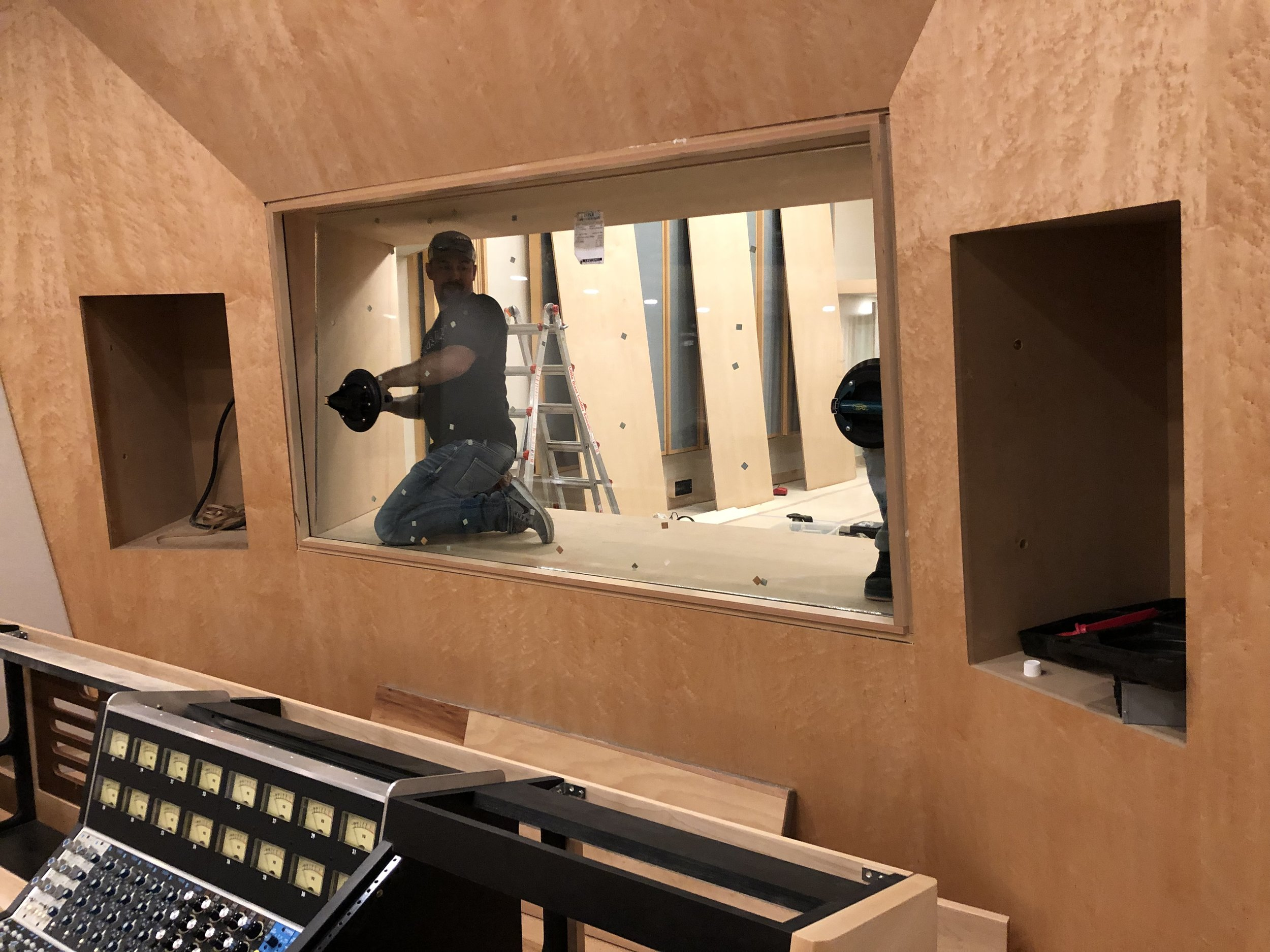 Getting the control room side glass set in studio 1.