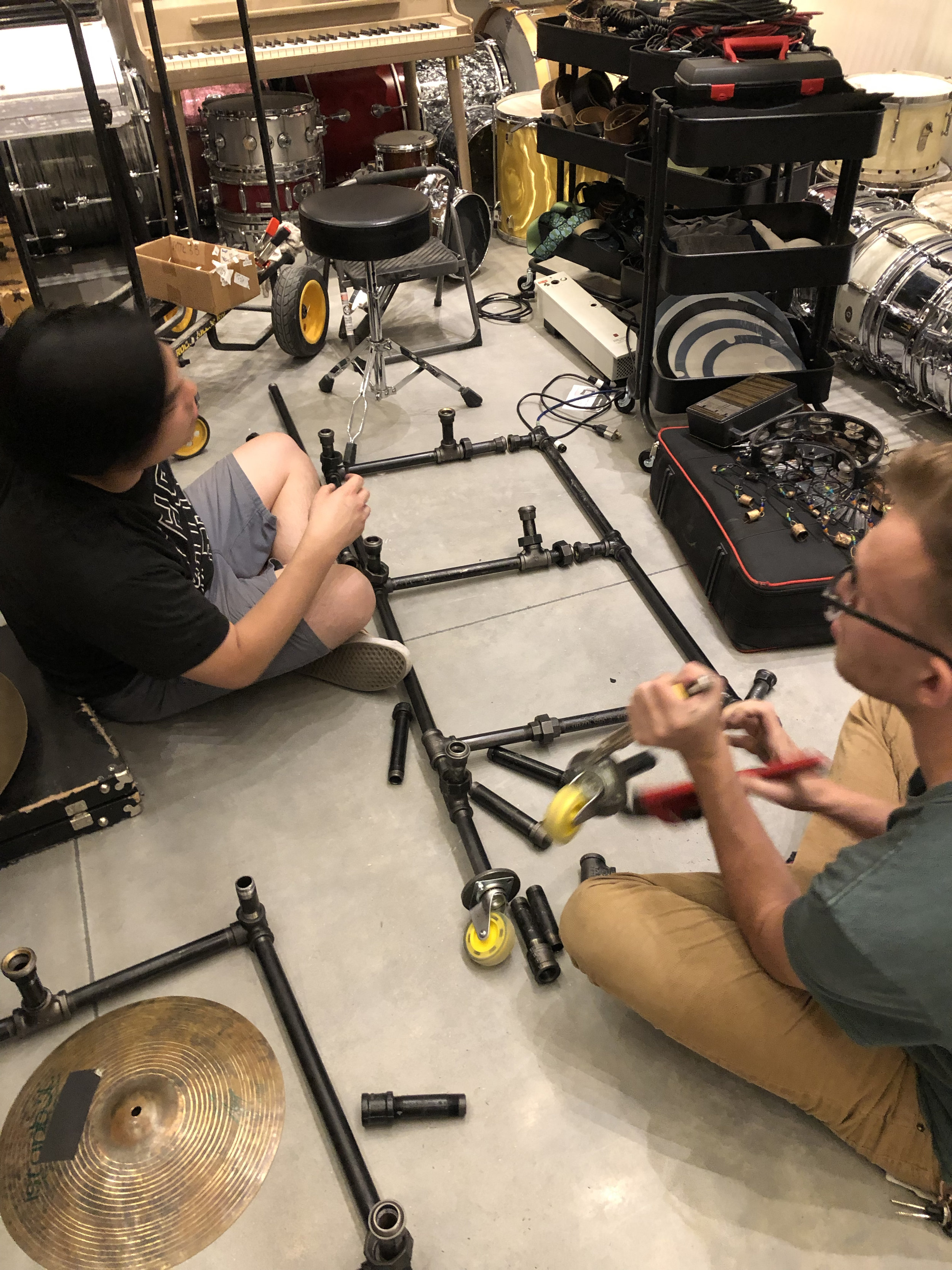 Trying to find a way to store and move cymbals around was proving difficult. We had them stored in multiple cymbal bags but we wanted a solution that would be mobile and hold all the cymbals. Ryan and Dan took our old rolling drum rack apart and got to work on a solution.