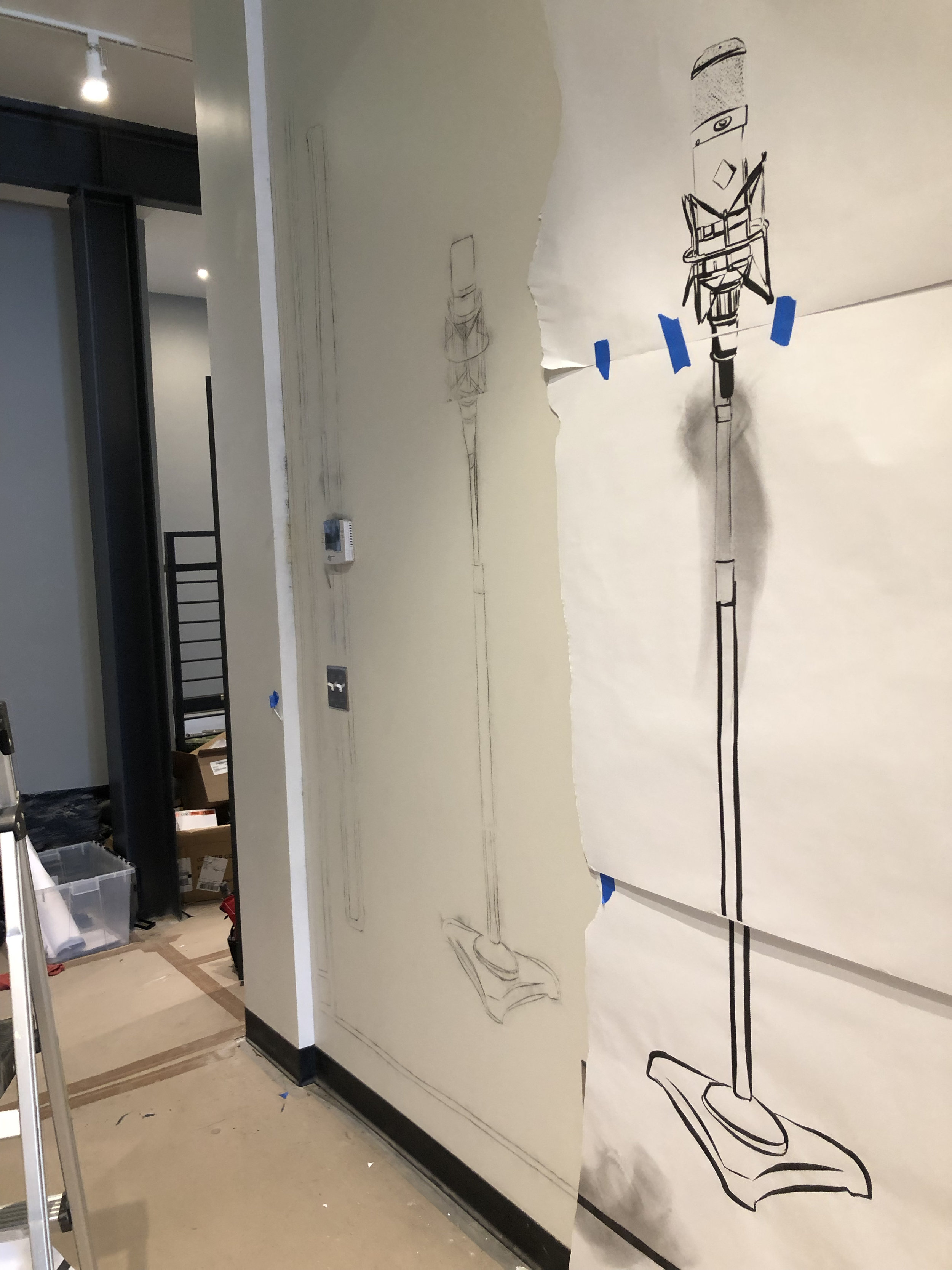 Jake printed the drawing out and then used a    pounce wheel    to perforate along the lines. Then the prints are hung in place and a    pounce pad    is used to beat chalk through the small holes on to the wall. You can see the chalk lines to the left where the paper has been removed.