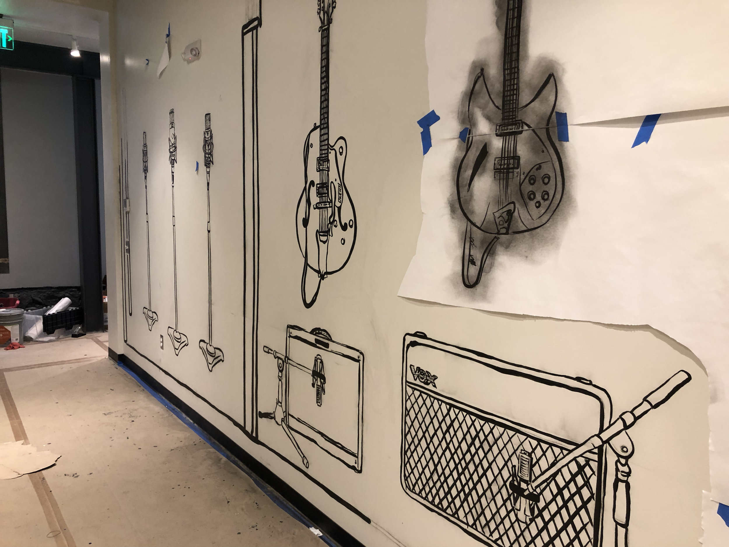 The final mural is basically an elevation of the entirety of Studio 2, so to the left is the small booth, where you see the three mics on stands, then the wall, then the tracking room where the guitars and amps are pictured, and then all the way down the wall to the window and the control room, everything lifesize and laid out where it is behind the wall.