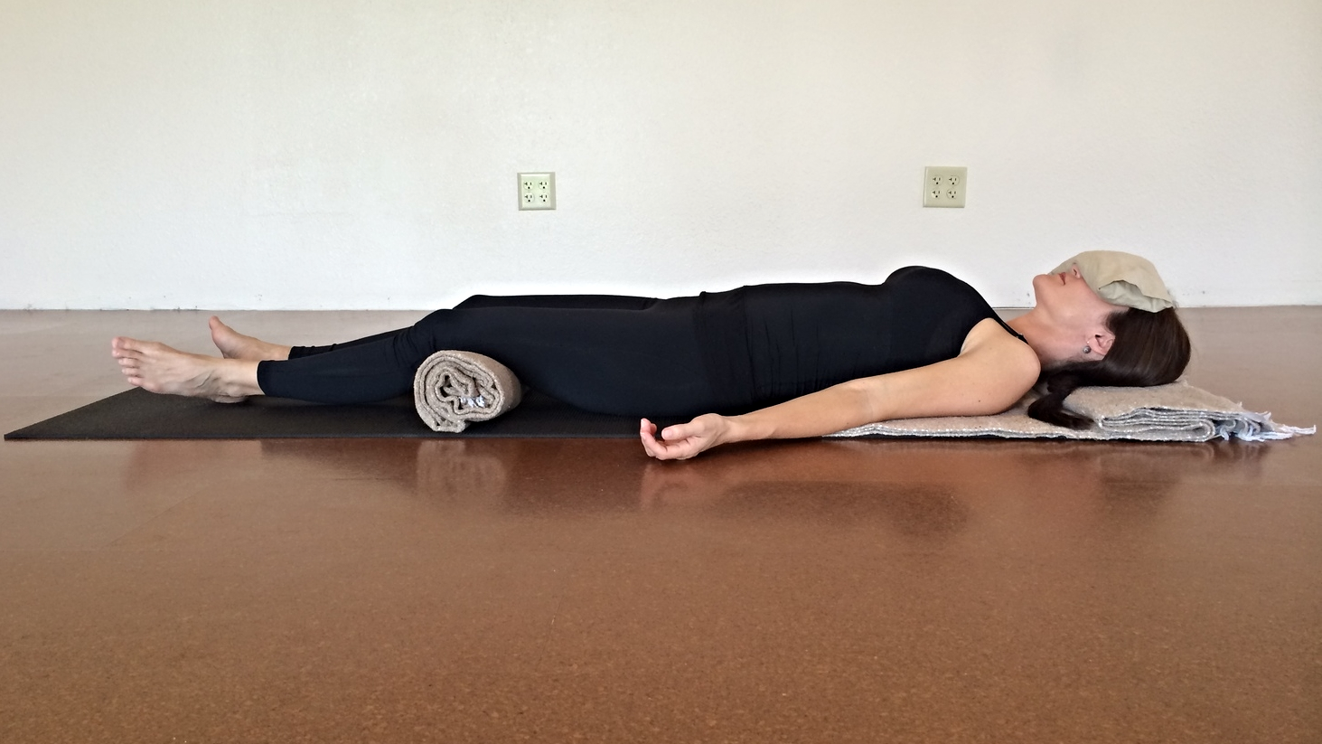 Savasana, or corpse pose, with the body lightly supported and an eye pillow to support rest.