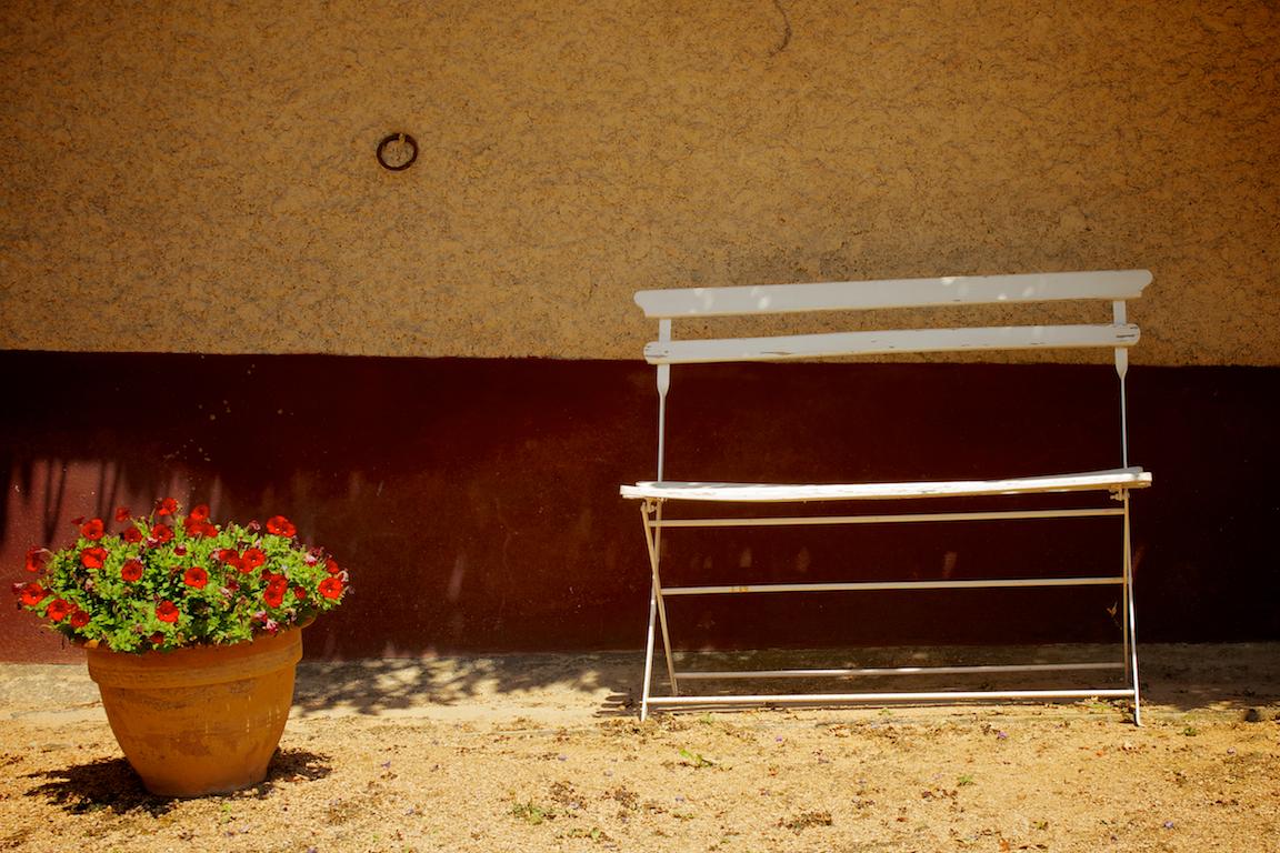 Zitbankje op de binnenplaats van Domaine Les Quatre Terres.