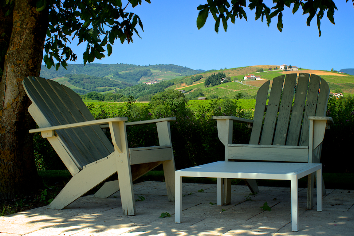 Sfeervolle zithoek bij het zwembad, met uitzicht over de wijngaarden.