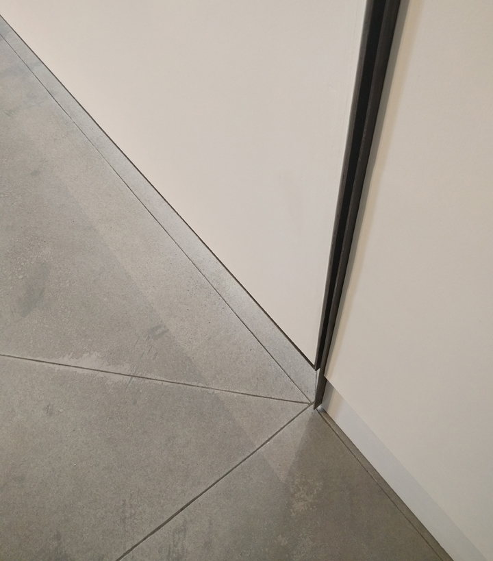 Convergence  Detail where floor and walls meet. New concrete floor, with radiant heat below, marks the place where static wall and pivot wall connect. Blackened steel frame and hinge outlines this moment of connection.