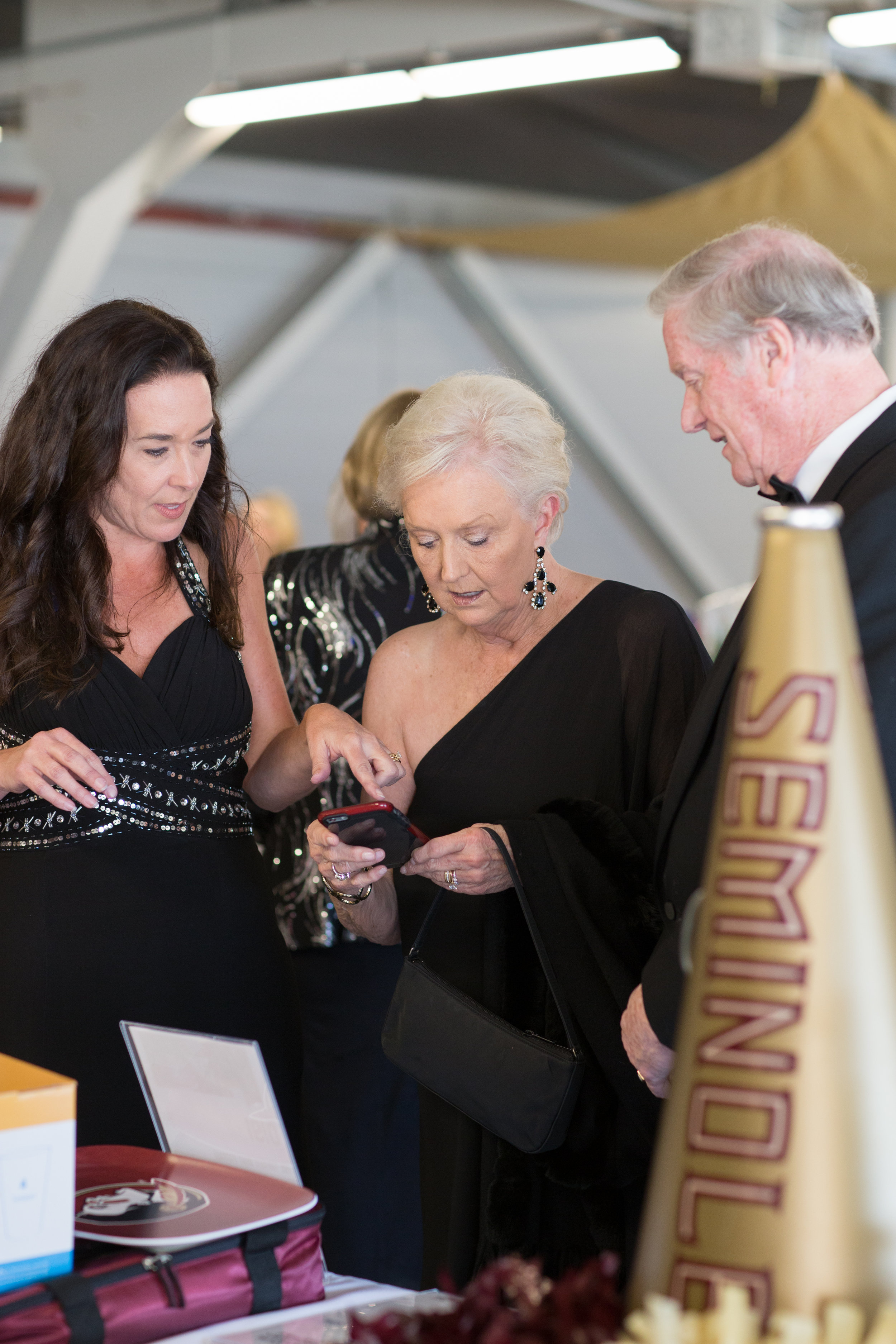 Volunteer Kimberly Adcock assists President and Mrs. Thrasher with online silent auction bidding