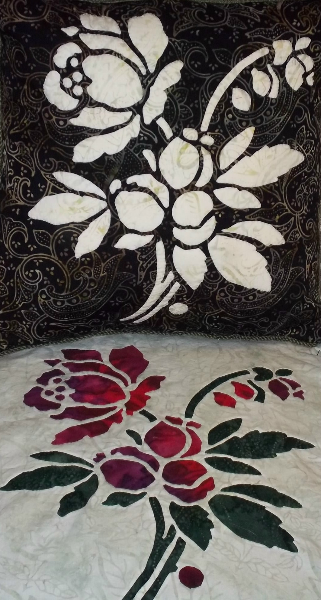 """Rose    pattern in batiks. top picture: 16"""" x 16"""" pillow with reverse needle turn applique. bottom picture: 16"""" x 16"""" block employing appliqued blossoms on a top of reverse appliqued stems and leaves."""