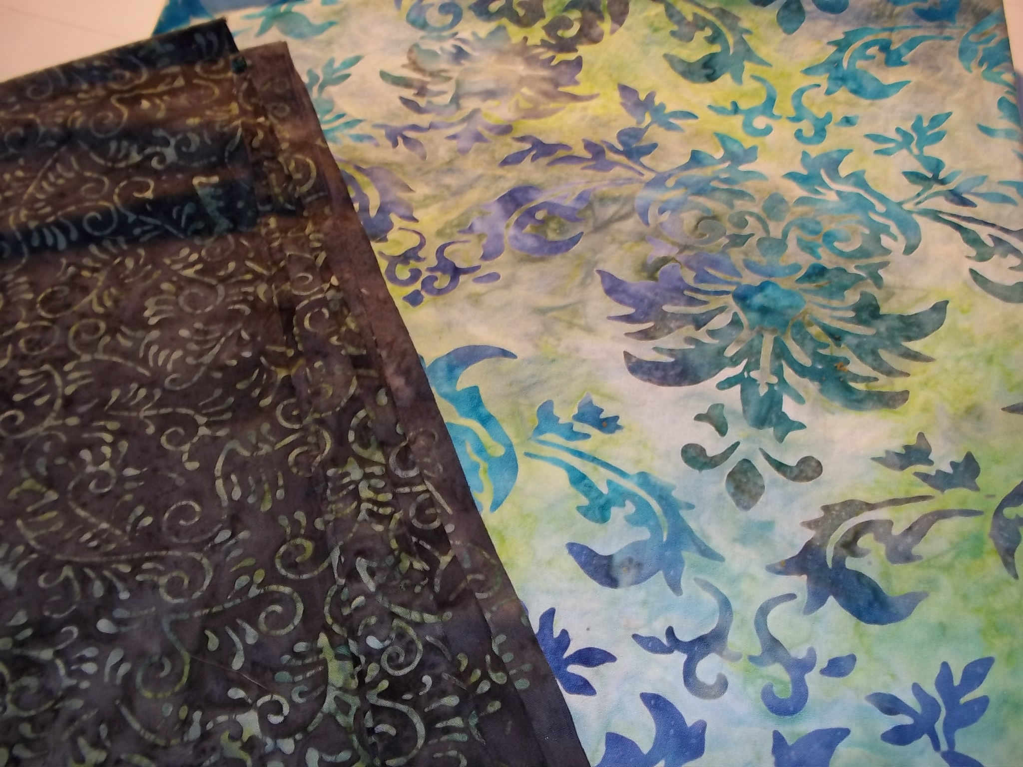 Grey with green swirls for top fabric. Blue and green multi-color patterned background.