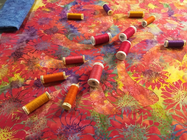 An assortment of thread colors to augment the design and fabrics to create a complete whole.