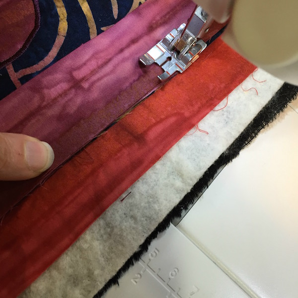 """Sewing binding on with 1/4"""" seam allowance."""
