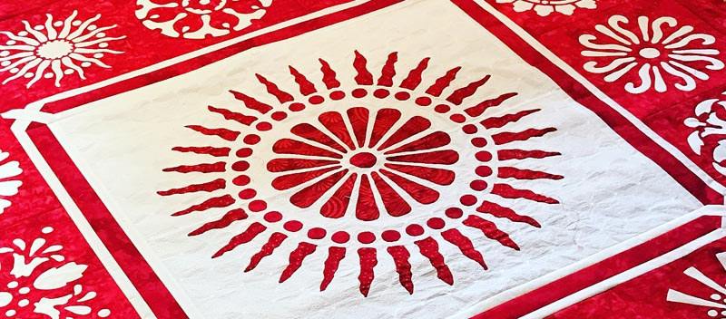 A Red & White quilt with lots of applique and reverse applique circles.