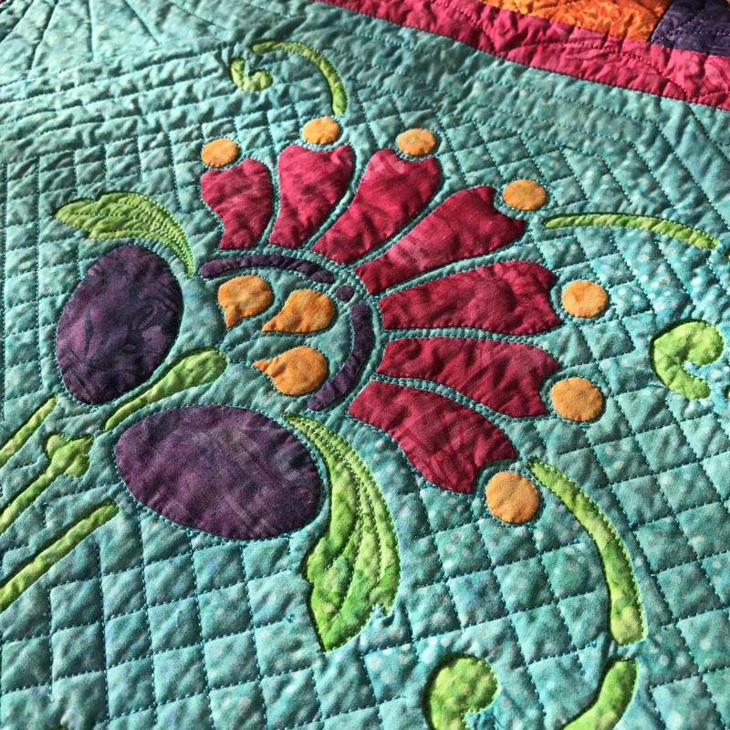 """Quilt in the green reverse applique space, in the ditch around the applique petals, and a 1/2"""" cross-hatch and frame."""