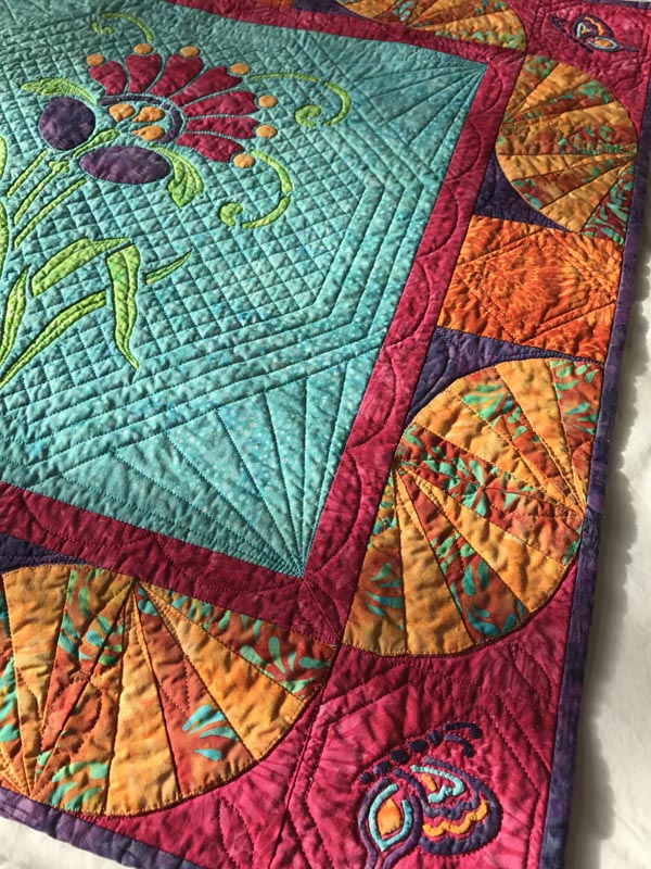 Quilted in the ditch around the butterfly wing bits and an octagon around the butterfly corner blocks, and a diamond in the dark orange squares.
