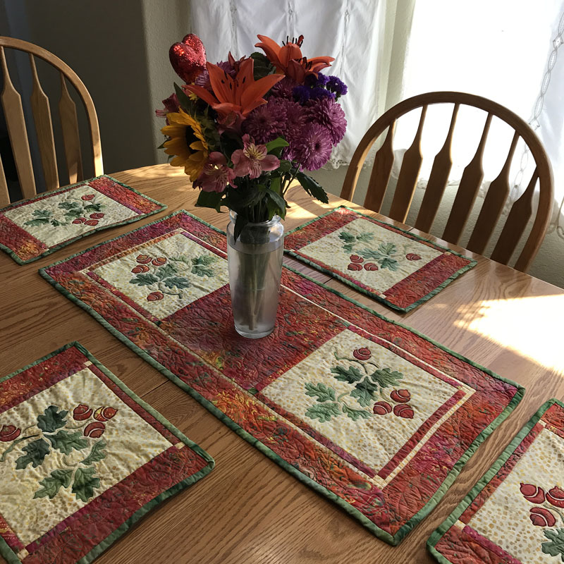 "Autumn's Promise table decor set.    table runner (16"" x 35""); placemats ( 10"" x 14""). Hand or machine reverse applique with applique, and machine pieced. Designed in fabrics by Timeless Treasures."