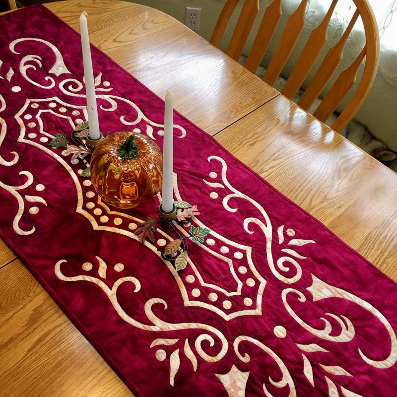"Abounding Grace table runner VIII   (20"" x 56""). Hand reverse applique. Designed for Batik Textiles Fall 2016."