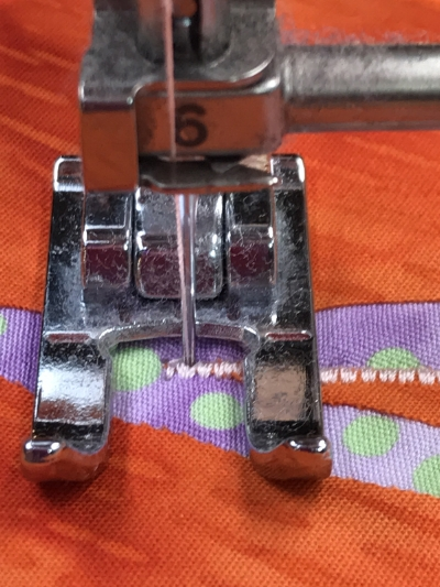 3. Lower the presser foot and take one stitch so the needle is down in the right hand position of the satin stitch. Raise the presser foot.