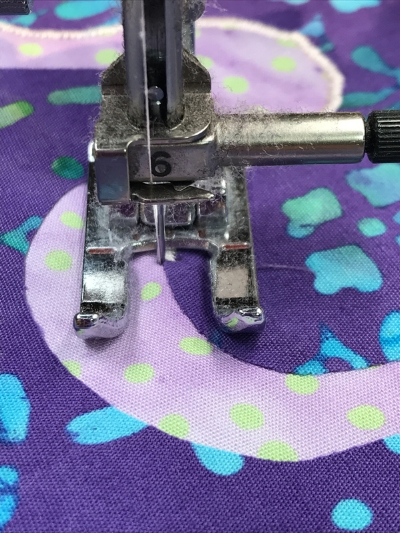 1. Time to pivot. I can tell because the presser foot is no longer perpendicular to my raw edge. I leave the needle down in the left hand position of the satin stitch, and raise my presser foot.