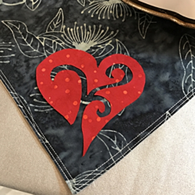 """Peel fusible paper off of red heart and position 1/2"""" from napkin edge."""