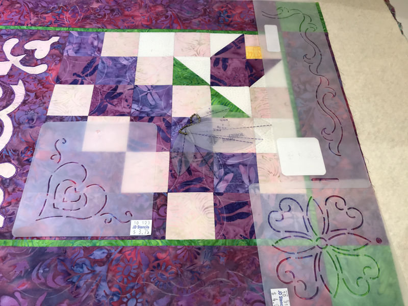 Getting ready to quilt. Auditioning quilting stencils.