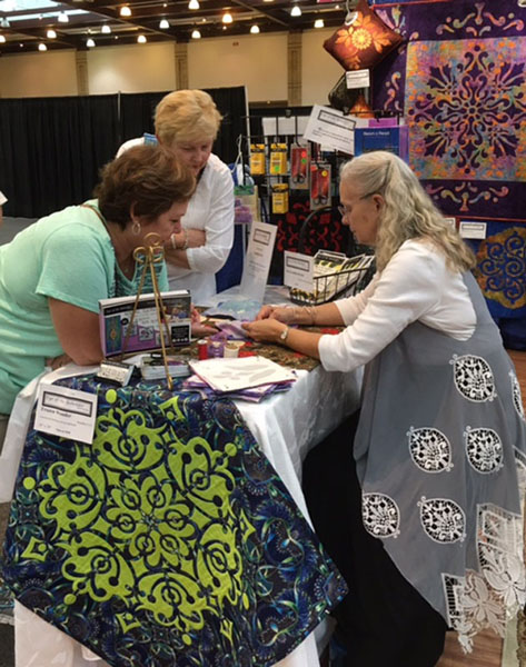 Margaret demonstrating her trace, baste, snip & stitch method for hand reverse appliqué at a quilt show.