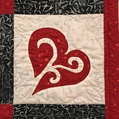 """6"""" reverse applique heart block from   Snowy Hearts table runner IX   (12"""" x 35""""). Hand reverse applique, machine quilted in the interior space and in the corners of the top fabric of the block using a stencil by Full Line Stencil."""