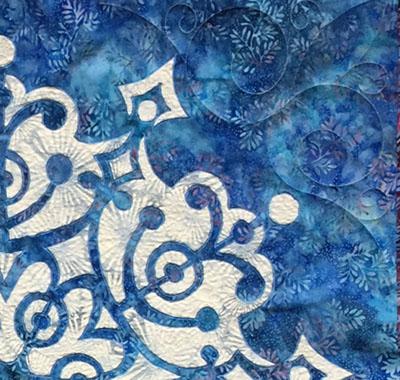 Frosty Frozen Wonder Quilt I  , center medallion corner. machine stitched. small stipple in reverse applique space, swirl in corner of top fabric. front view.