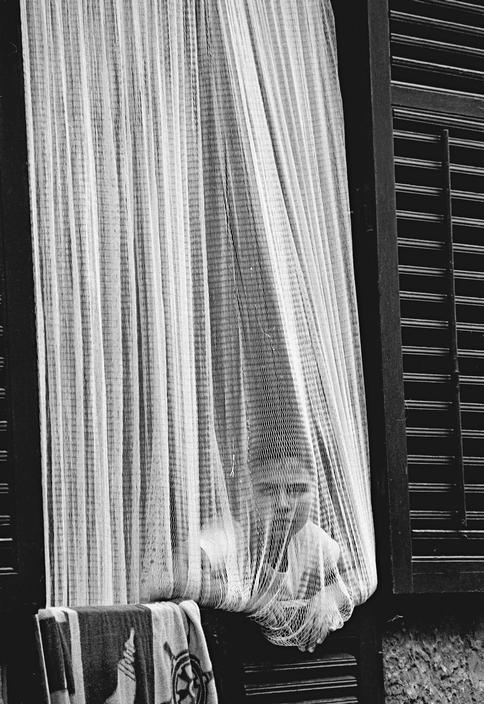 Ferdinando Scianna - Italy, Sicily, Bagheria: woman in front oh her hous back of the net.