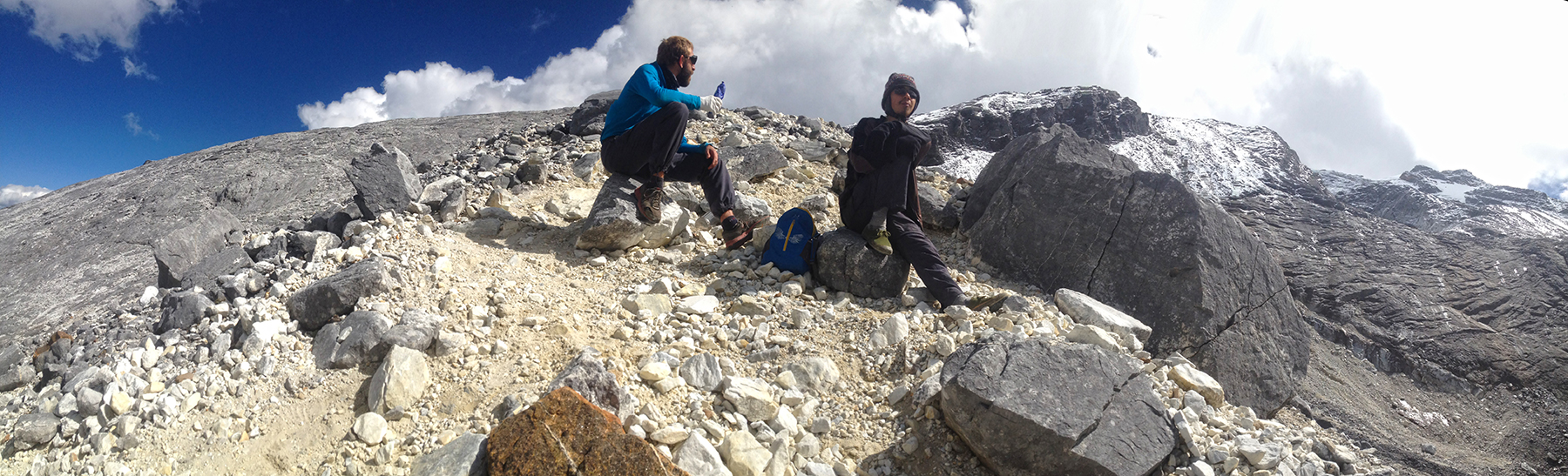 Nico and Louis relax on the upper moraine leading to the final slab and glacier entrance during acclimatization day.