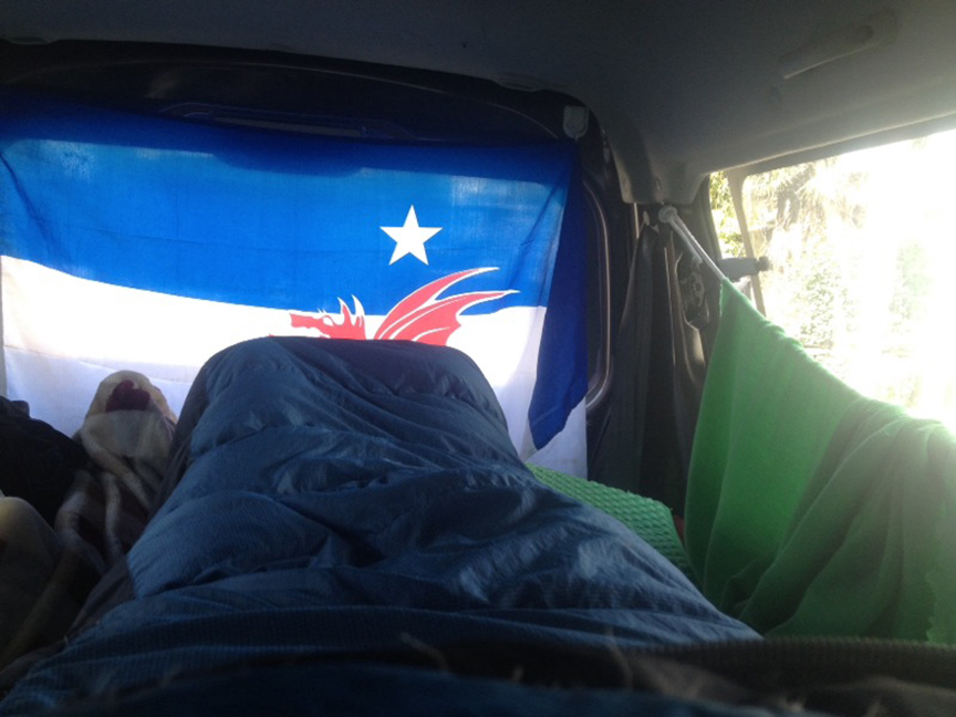Morning in the van. The curtains actually sit atop the passenger handles and can cover the windows.