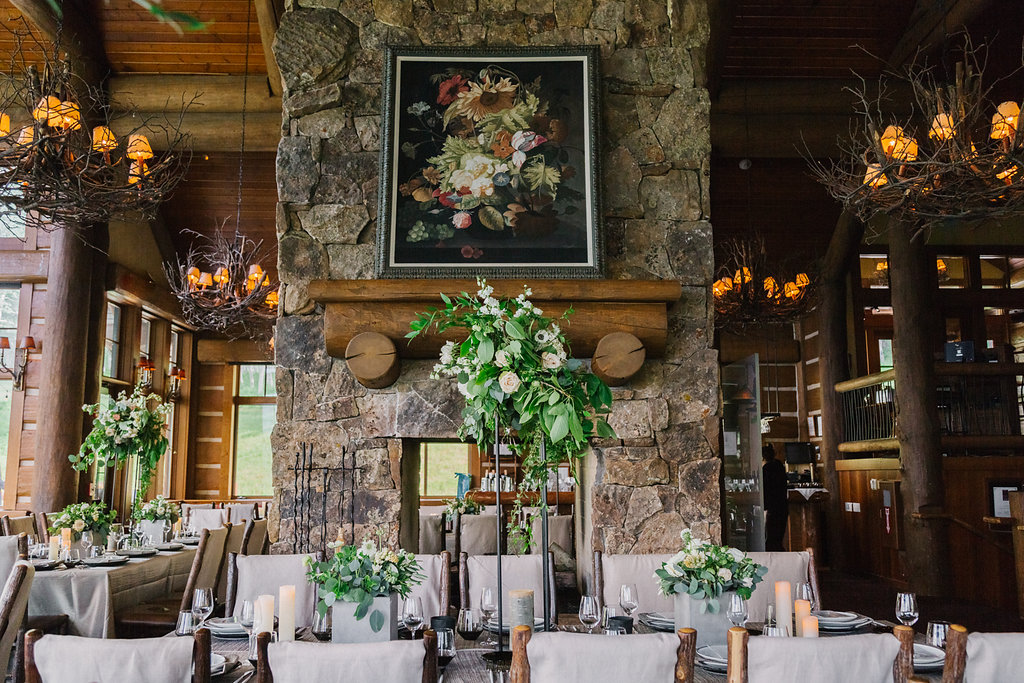 Cabin Fireplace and lush wedding centerpieces at reception.