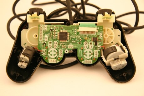 """The differences in the weights on each motor allows the controller to produce a greater range of sensations than would be possible with matched weights. Image reproduced from """"Playstation 3 SIXAXIS dissection and Dual Shock comparison"""" by G. Block, December 1, 2006,  IGN .  Copyright 2015 by Ziff Davis."""