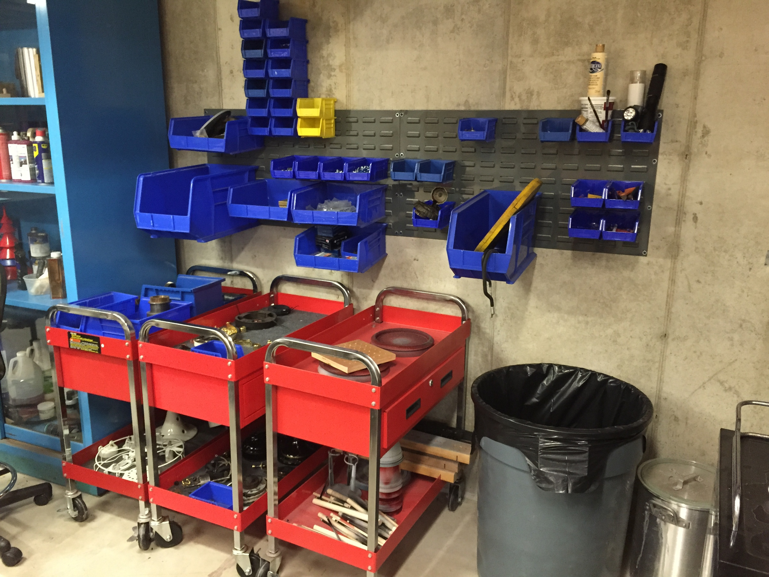 WIP carts with storage bins on a wall mounted rack.