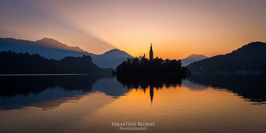 The sun showing its first rays above Lake Bled and the church on the island