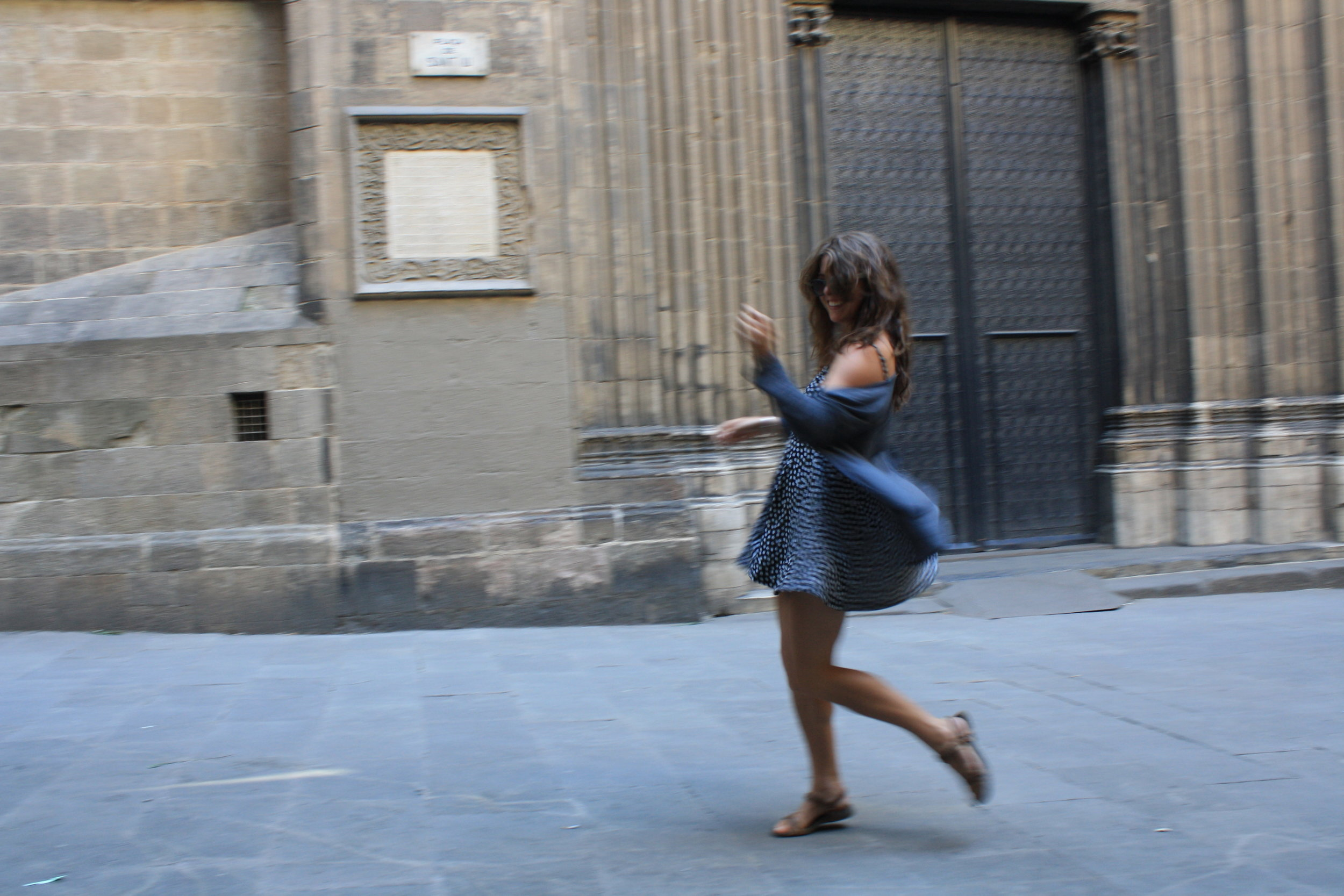 Dancing to a busker in the shadow of a cathedral courtyard in Barcelona, age 22. Photo by future husband.