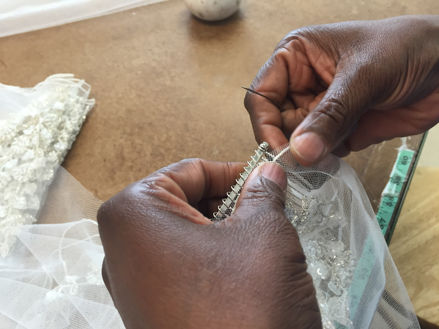 SEWING  - There is no substitute for the hand sewing of combs, lace appliqués, and other refinements that create a beautiful veil. Edging and other operations although machine sewn, are guided by a human hand..