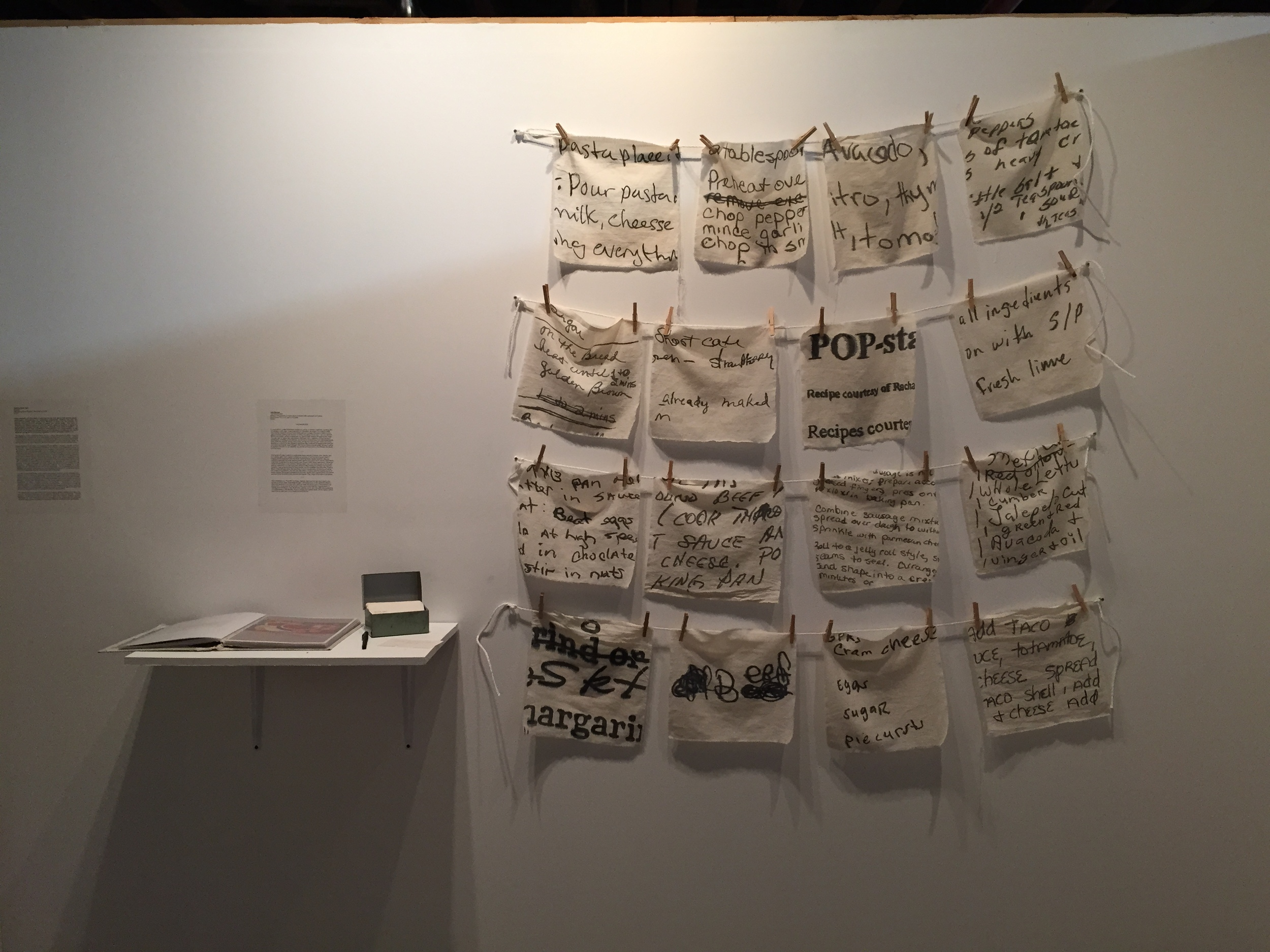 "Julia Rooney THE RECIPE BOX Medium: Ink painted on cotton fabric; installed with clothespin and twine Dimensions: 12"" x 12"" each; (16 total) 2015  Statement: In June 2014, I mailed individual recipes to a group of women I had been working with at a shelter in Brooklyn. I was inspired by a discussion we began the previous week about family traditions around food. Along with the recipes, I included a blank card in every envelope, asking each woman to share one recipe of her own. I set up a RECIPE BOX at the shelter, where I asked them to deposit their recipes throughout the week. The plan was to collect the submissions and then cook a selection of them during a subsequent workshop. In the kitchen, we worked in small groups and collectively taught each other the recipes. At the dining table, we ate the meal we had made, and jointly decided on a theme for the following workshop. We continued throughout the summer, and at the end visited Judy Chicago's The Dinner Party at the Brooklyn Museum, giving us another context for our identities as women, and our work in the kitchen, the studio and the world. ***This series of cotton napkins is inspired by these women's recipes, their stories, and our collaboration. Each napkin includes an excerpt of one woman's recipe, which I traced and hand-painted onto the fabric. Cooking these recipes together was our collective approach to understanding them: where they came from, how to make them, what their significance to each woman was. It was a fairly literal experience, following a recipe's instructions in the kitchen. Months later, I am now working solo in the studio, and my experience has become more abstract. My process of painting their text has become a new gesture towards these words and the activities they describe. Painting them, I have thought about the specificity of one's handwriting, the spacing of words, the choice of ingredients, the way one describes a method, and the original source of these recipes. Some were printed from the web, others were passed down, and others seemed to be invented by the women themselves. This range of formats is expressive.***This installation is a ""first life"" for these napkins: they have not yet been used in the kitchen or at the table. Essentially though, I conceived them to be utilitarian objects. After this exhibition, my hope is for them to enter the living space of the kitchen and dining room, to be used by the hands of the community that first inspired them. In subsequent workshops, they will become stained, worn, and ultimately personalized by our experiences in the kitchen. Just as recipes are passed down, these napkins will be used and re-used over many meals, by many hands."