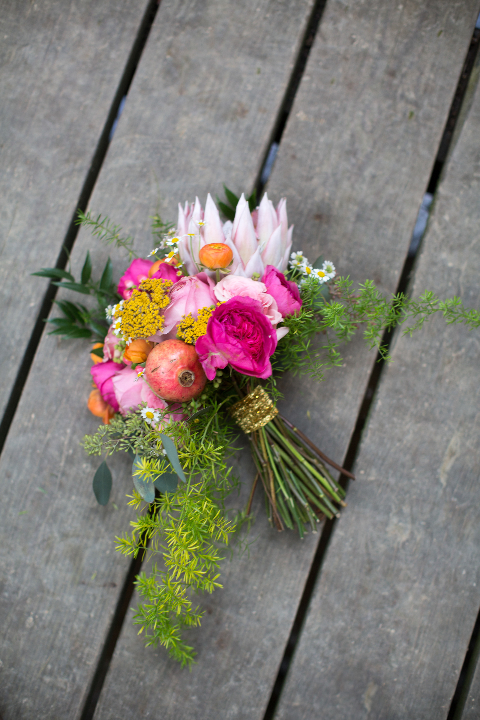 Bright bridal bouquet with a pomegranate and king protea