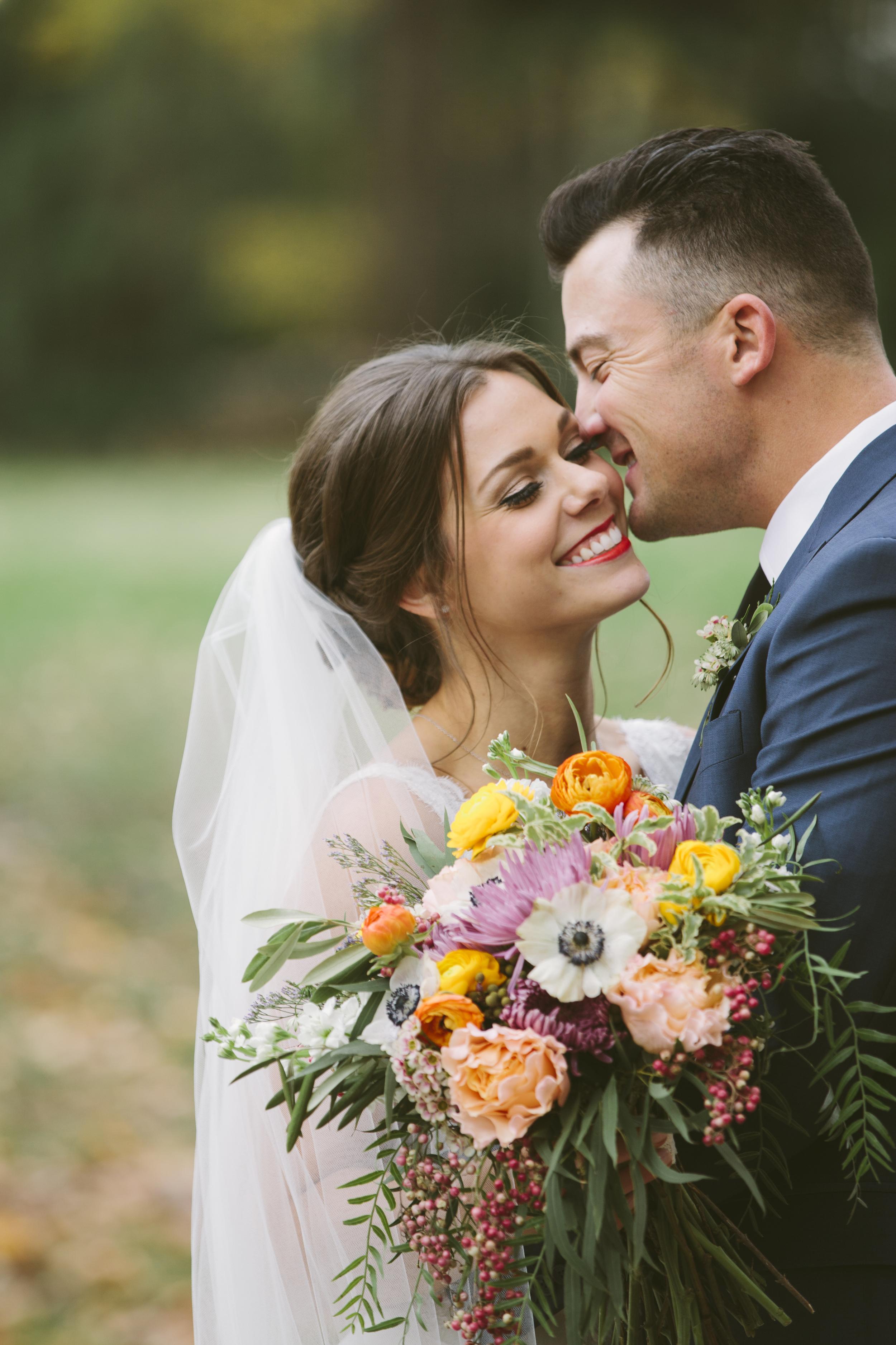 Bright bridal bouquet with garden roses, ranunculus, anemones, and pepperberries // Nashville Wedding Florist