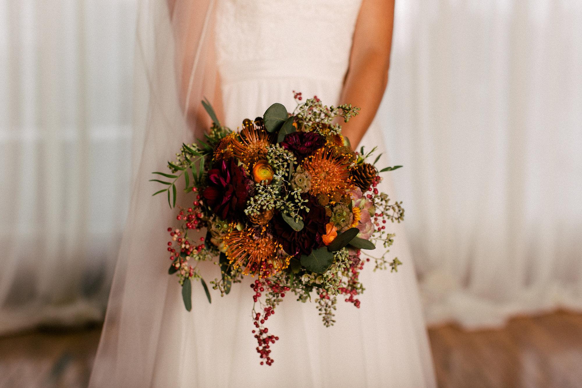 Fall bridal bouquet with pincushion protea, dahlias, and pinecones // Nashville Wedding Florist