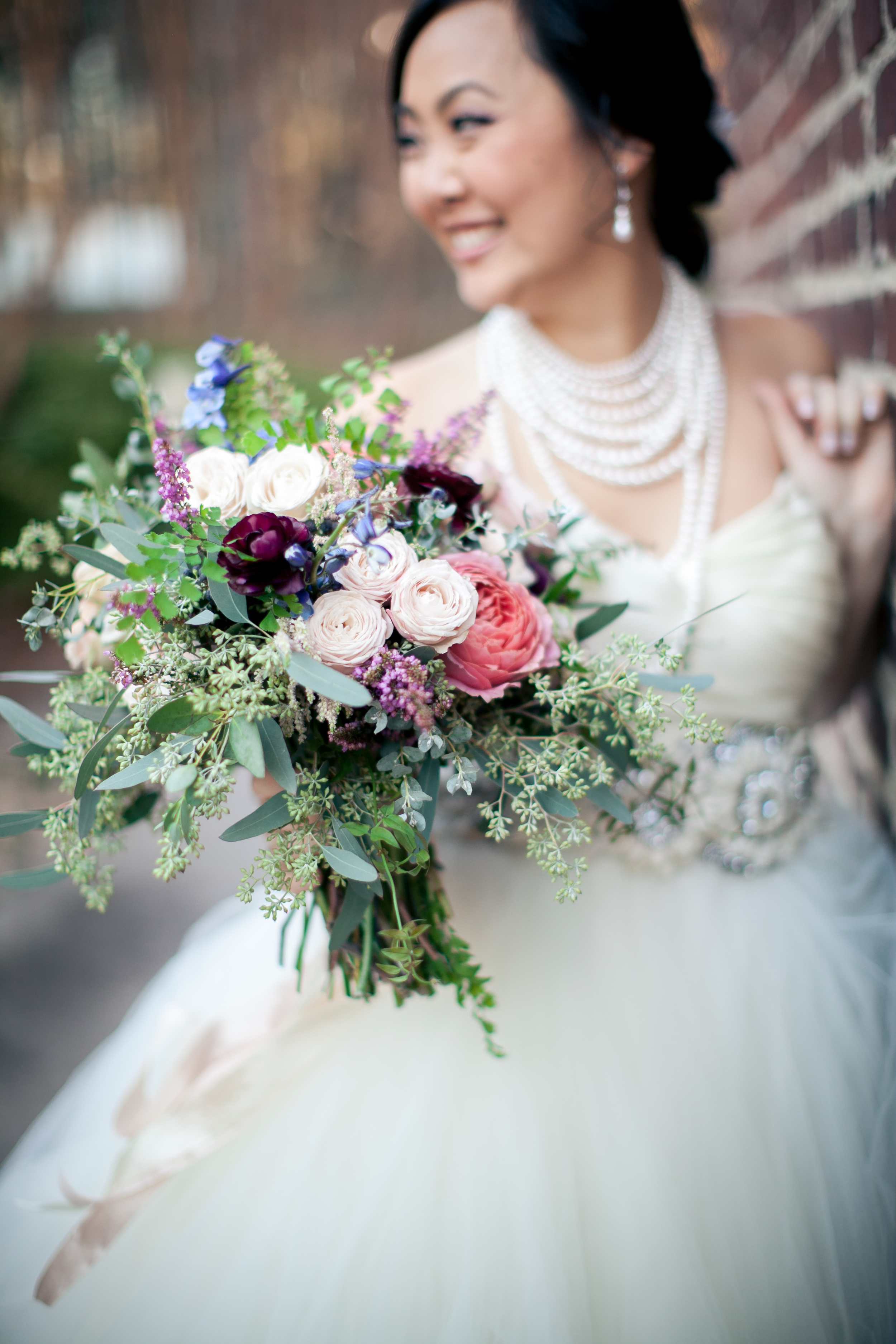 Romantic tulle wedding dress paired with organic, trailing bouquet
