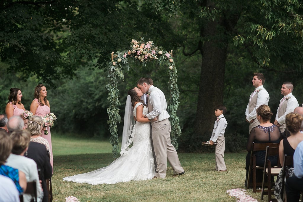 First Kiss under lush floral and greenery arbor // Tennessee Florist